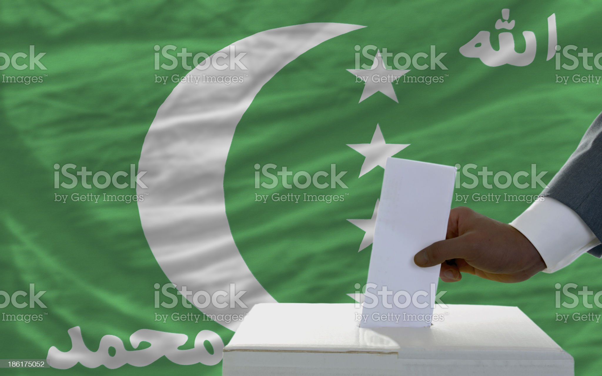 man voting on elections in front national flag of comoros royalty-free stock photo