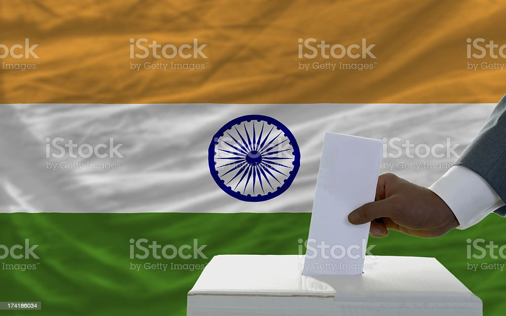 man voting on elections in front of national flag india royalty-free stock photo