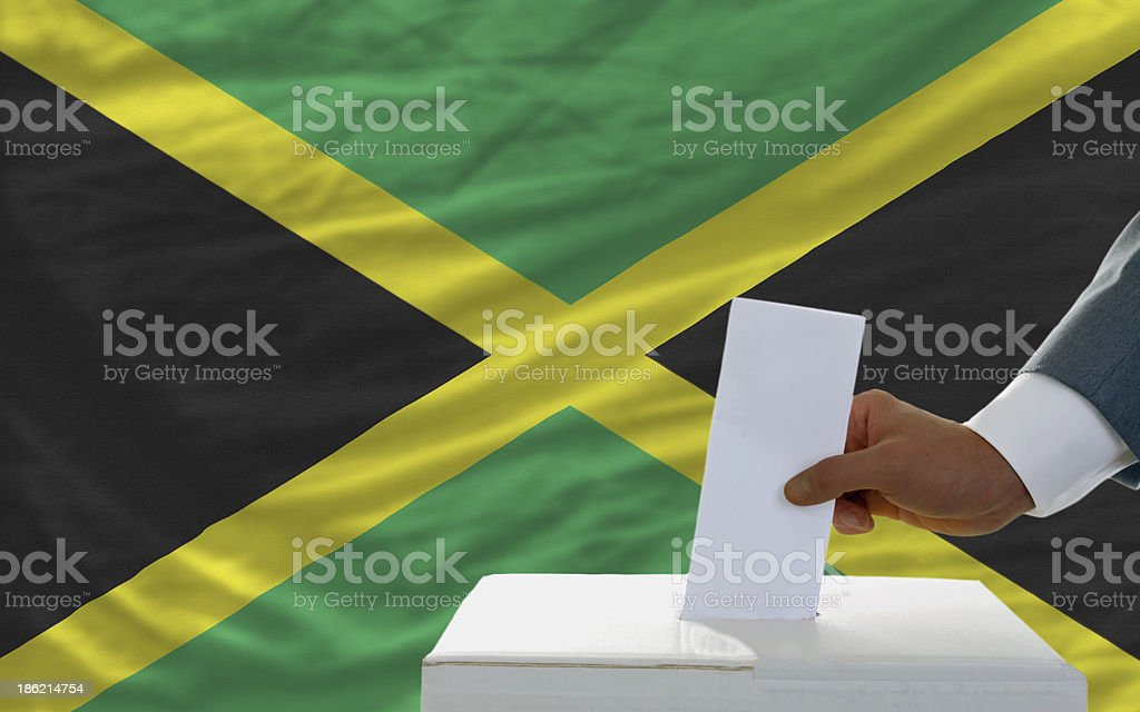 man voting on elections in jamaica front of flag royalty-free stock photo