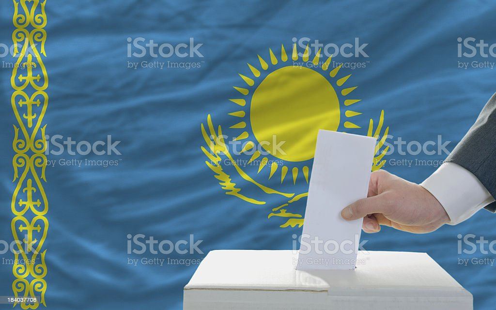 man voting on elections in kazakhstan front of flag royalty-free stock photo