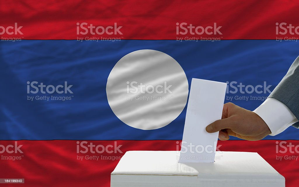 man voting on elections in laos front of flag royalty-free stock photo