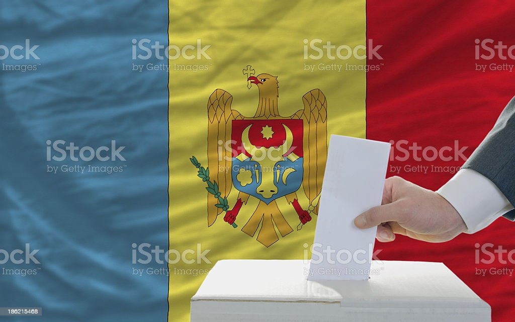 man voting on elections in moldova front of flag royalty-free stock photo
