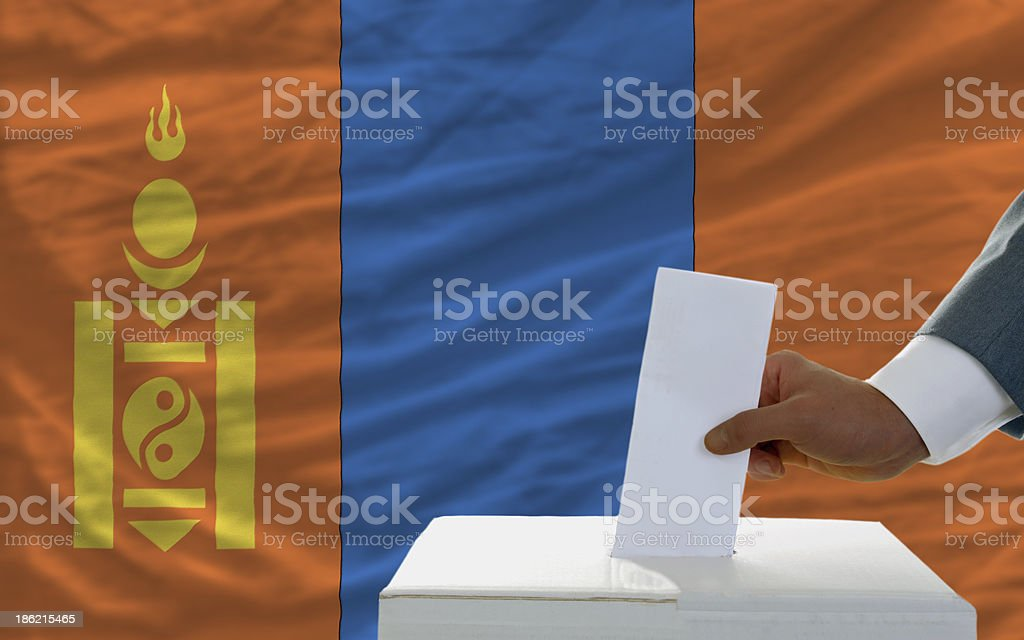 man voting on elections in mongolia front of flag royalty-free stock photo