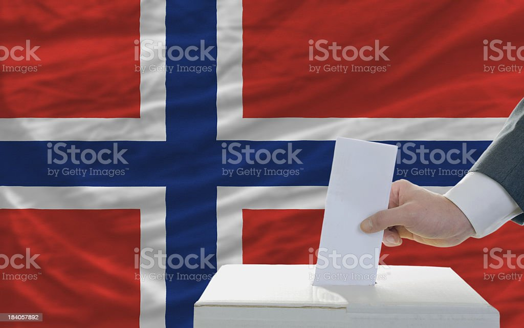 man voting on elections in norway front of flag royalty-free stock photo