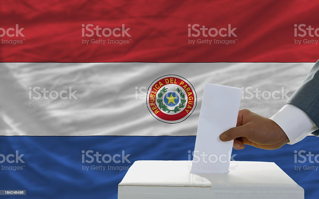 man voting on elections in paraguay front of flag royalty-free stock photo