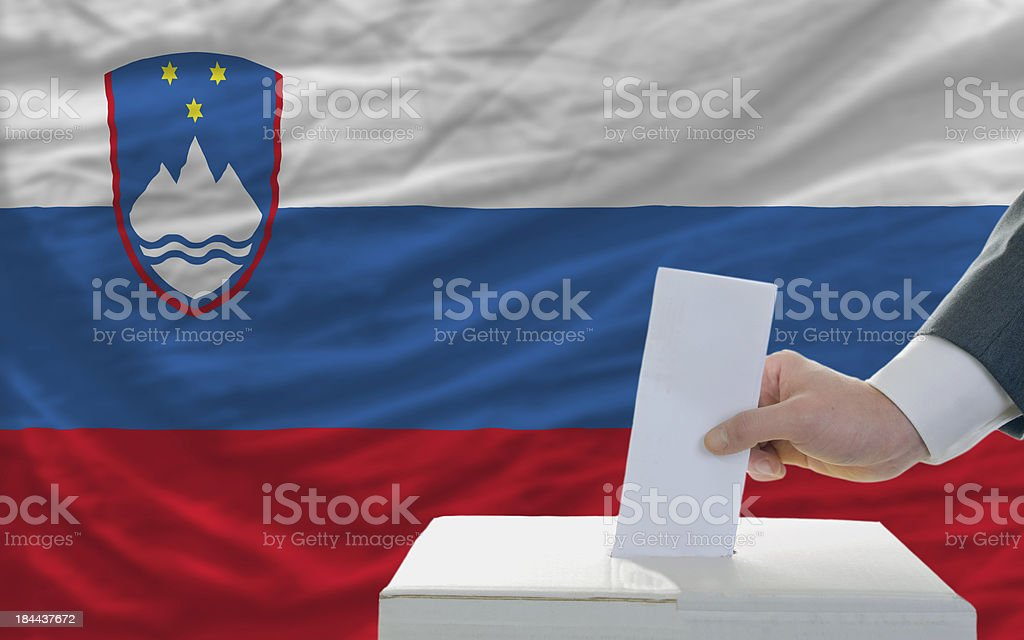 man voting on elections in slovenia front of flag royalty-free stock photo