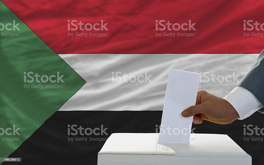 man voting on elections in sudan front of flag royalty-free stock photo