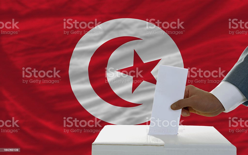 man voting on elections in tunisia front of flag royalty-free stock photo