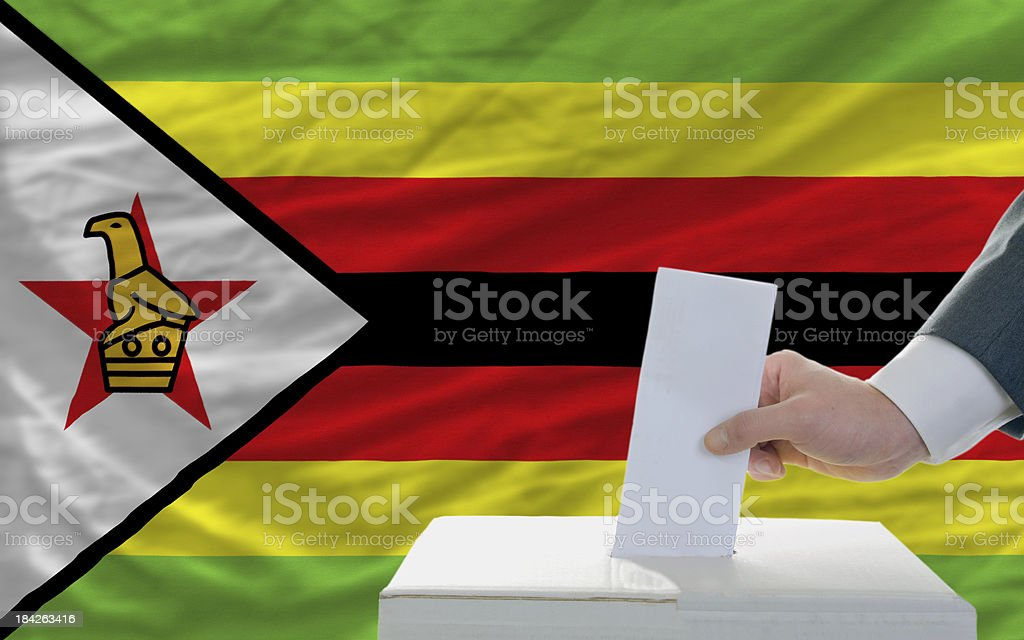 man voting on elections in zimbabwe front of flag royalty-free stock photo