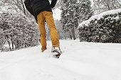 man wades in snow winter park during hard snowfall