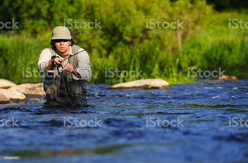 A man waist deep in a river fishing stock photo