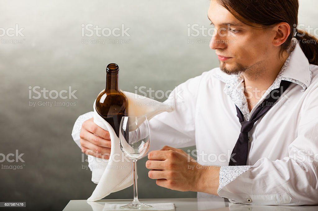 Man waiter pouring wine into glass. stock photo