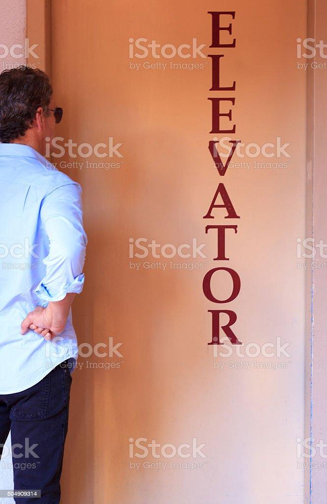 Man Waiting for Elevator, Orange Background stock photo