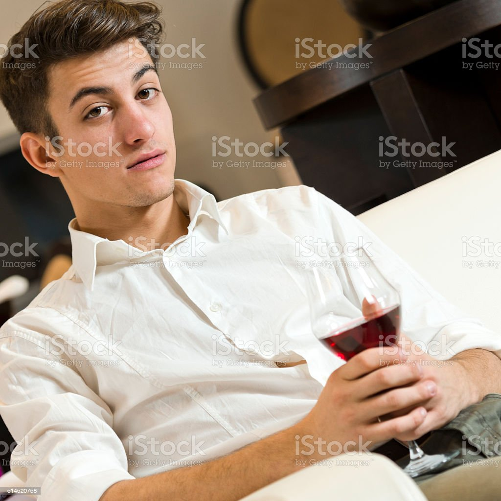 Man waiting on the sofa with a glass of wine stock photo
