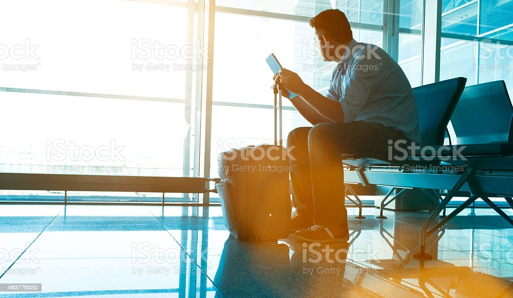 Man waits for plane at airport and looks for flight stock photo