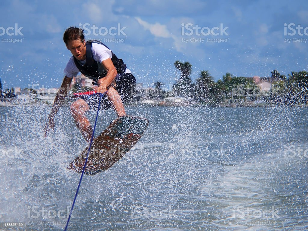 Man Wakeboarding Jump Kicks Up Water Spray stock photo