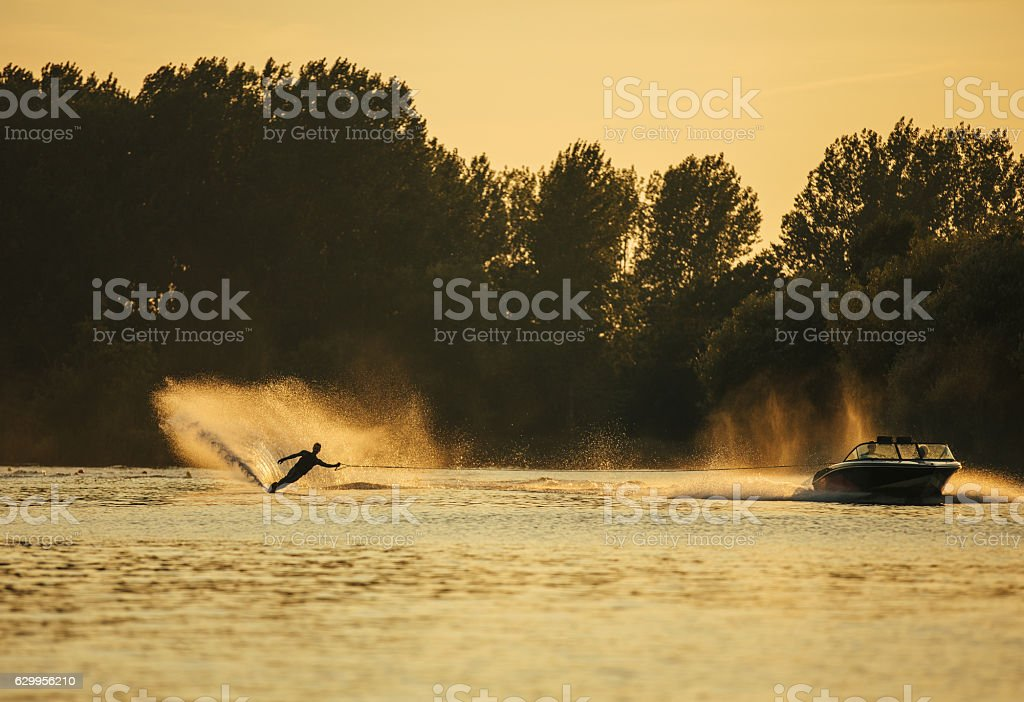 Man wakeboarding on lake behind boat stock photo