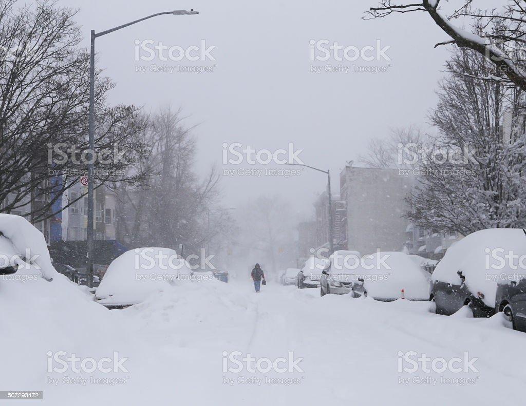 Man walk along snow covered street stock photo