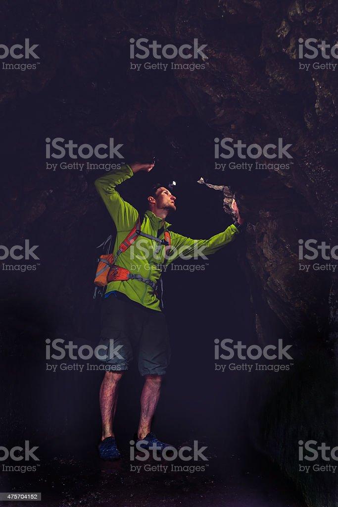 Man walk in dark cave underground stock photo