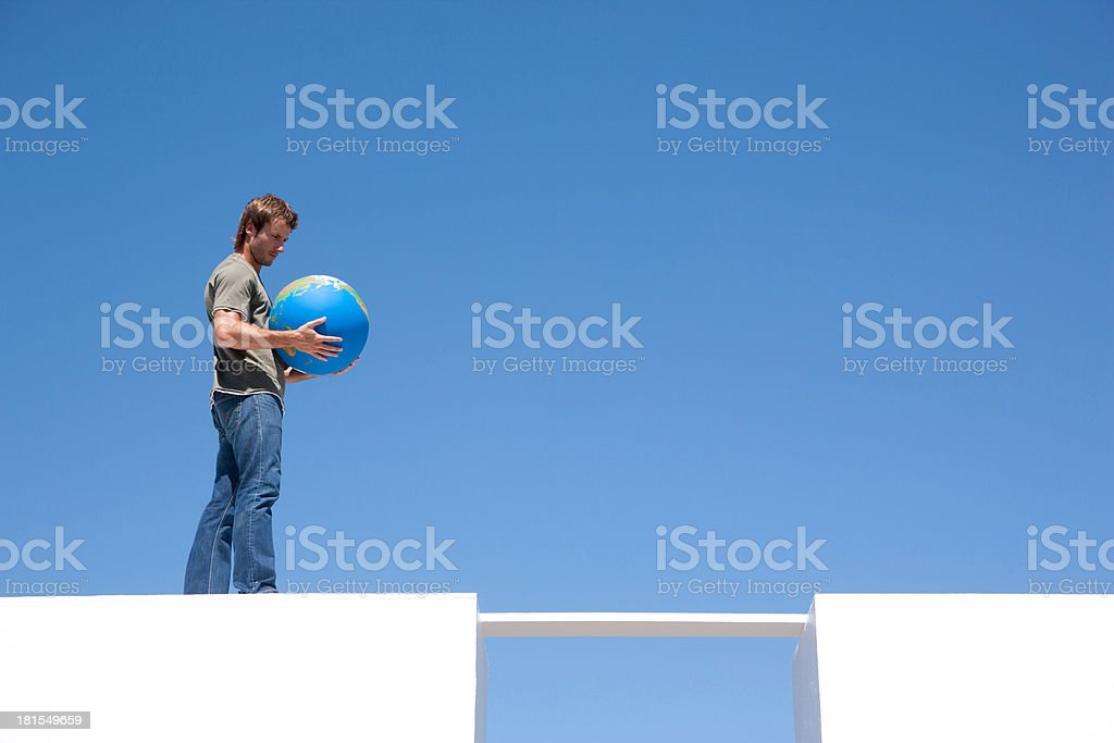 Man walking across plank with globe outdoors stock photo