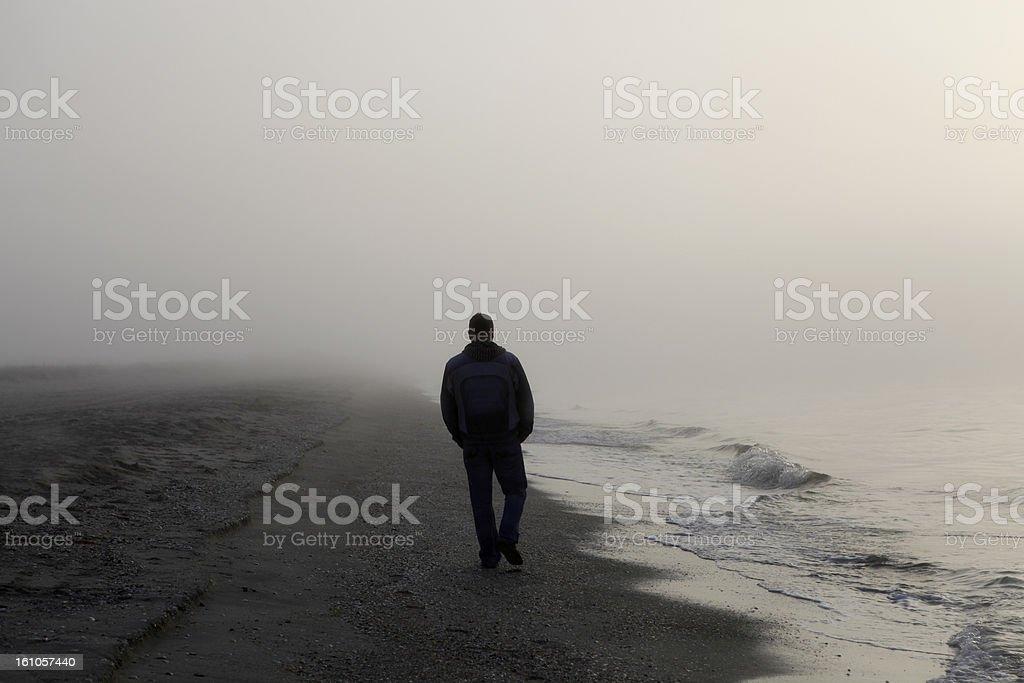 Man walking alone on a foggy beach stock photo