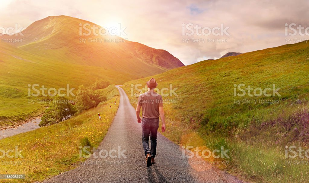Man walking alone on country road toward rising sun stock photo