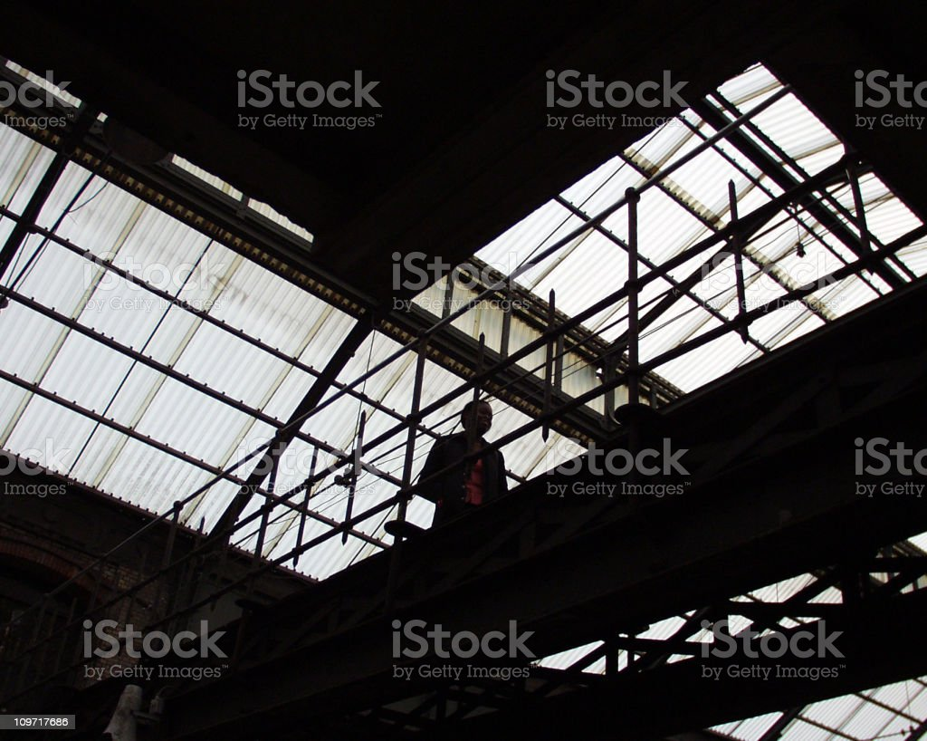 Man Walking Along Factory Catwalk stock photo