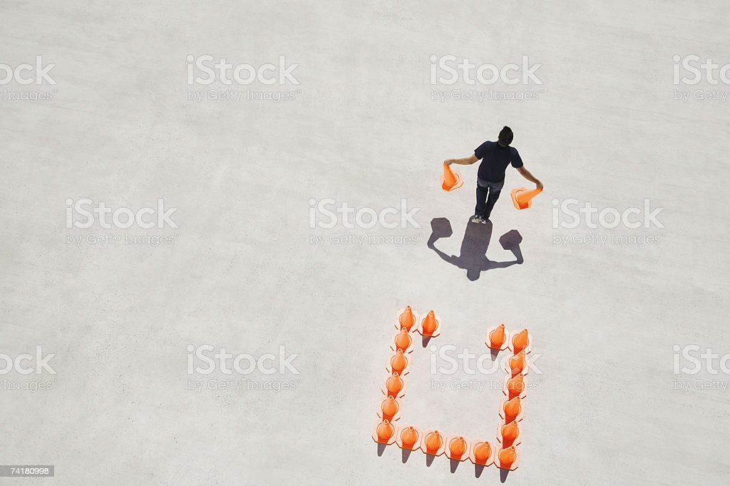 Man walking away from box of traffic cones with two royalty-free stock photo