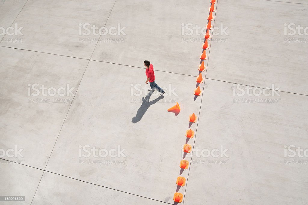 Man walking away from row of traffic cones with one misplaced stock photo