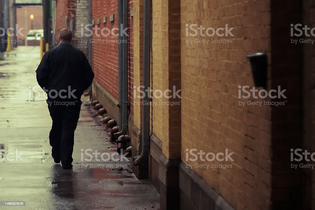 Man walking away in an alleyway on a rainy day stock photo