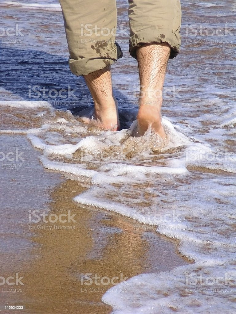 Man walking barefood on the beach royalty-free stock photo
