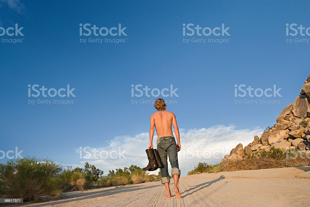 Man walking barefoot on a road stock photo