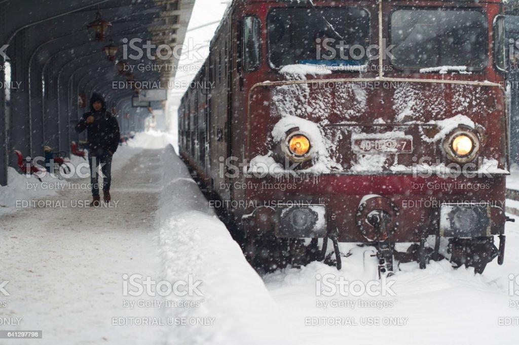 Man walking by a frozen train locomotive stock photo