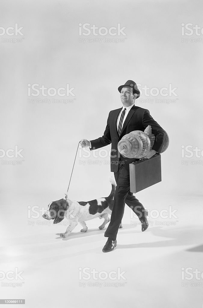 Man walking dog with briefcase and pedestal, smiling stock photo
