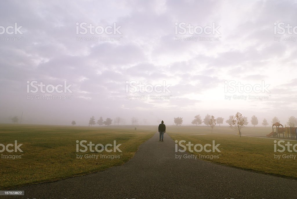 A man walking down a road into the fog stock photo