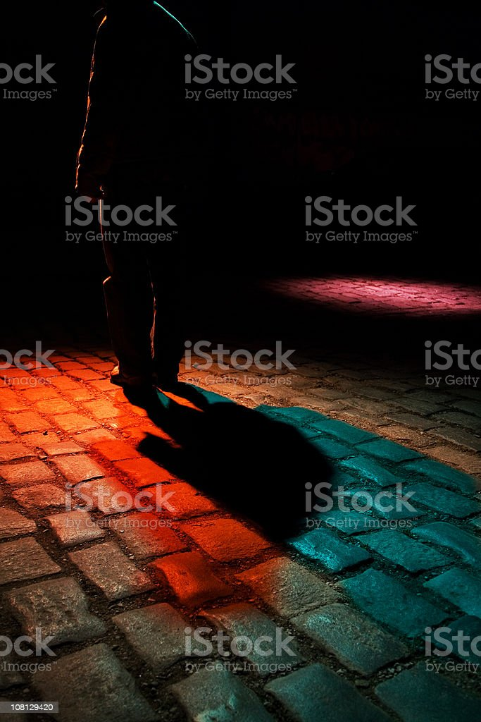 Man Walking Down Dark Cobblestone Street, Low Key royalty-free stock photo