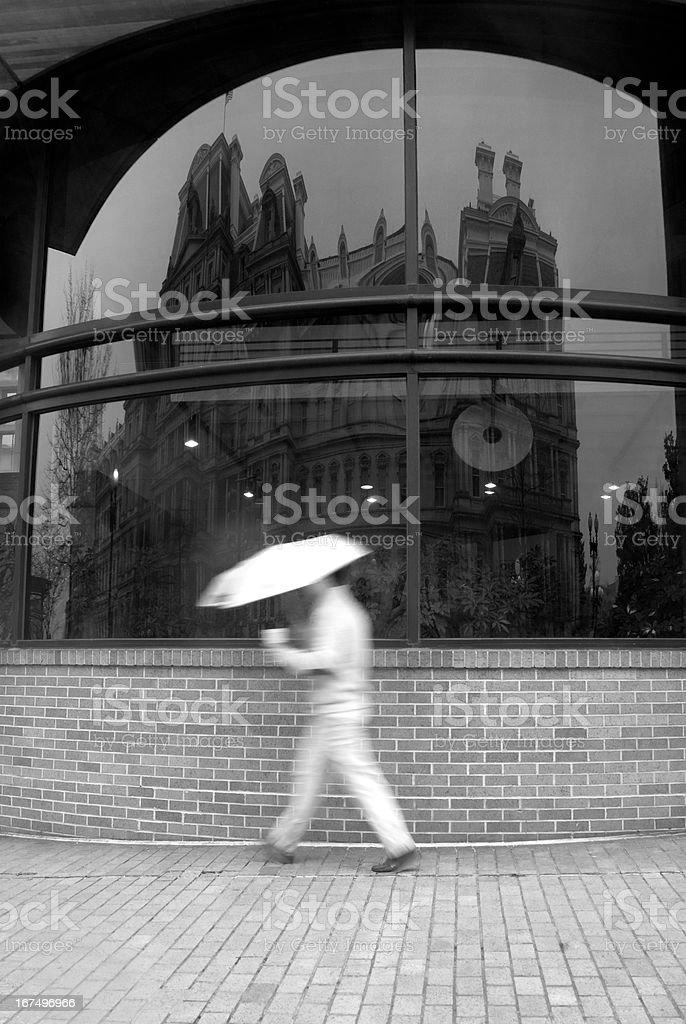 Man walking during rainstorm. stock photo
