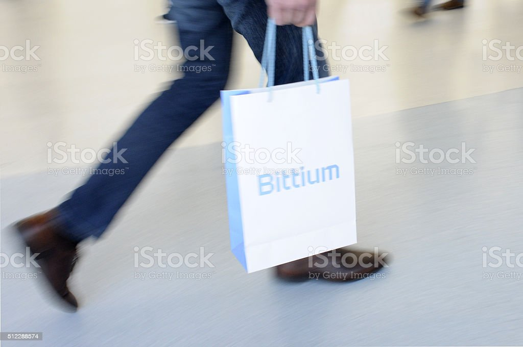 man walking fast with a paper bittium bag stock photo
