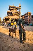 Man walking goat through ancient cobbled square Bhaktapur Kathmandu Nepal