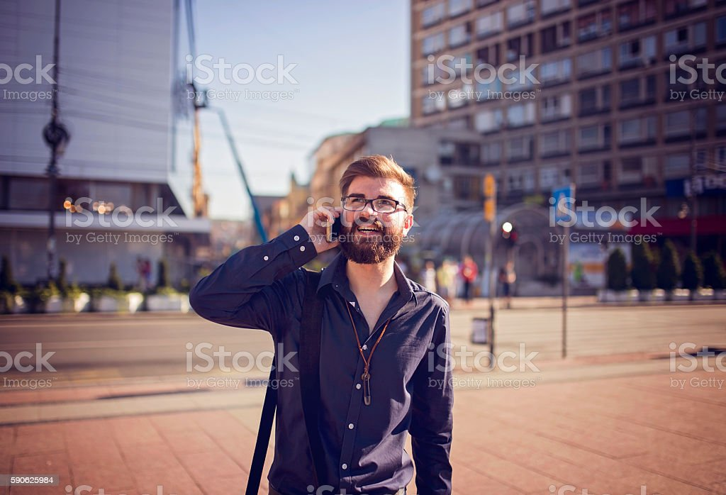 Man walking in center of city and making phone call stock photo