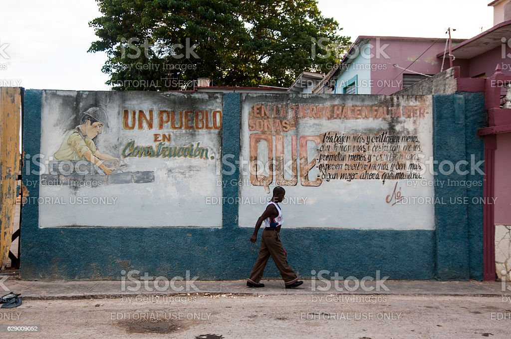 Man walking in front of Che Guevara mural in Cuba stock photo