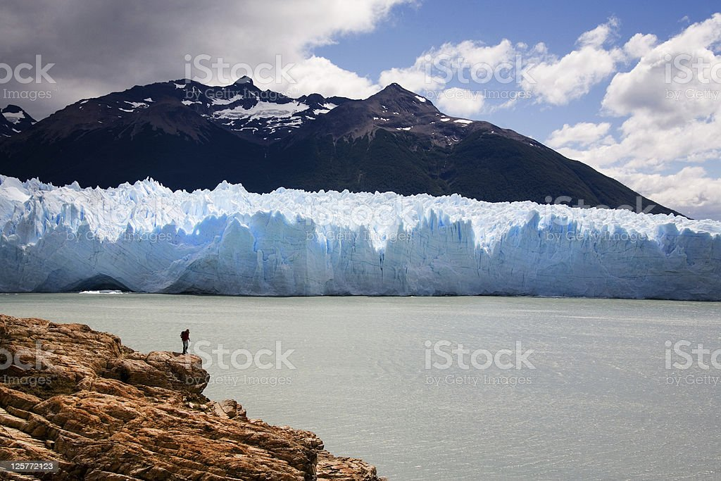 Man walking in front of  Perito moreno glacier stock photo