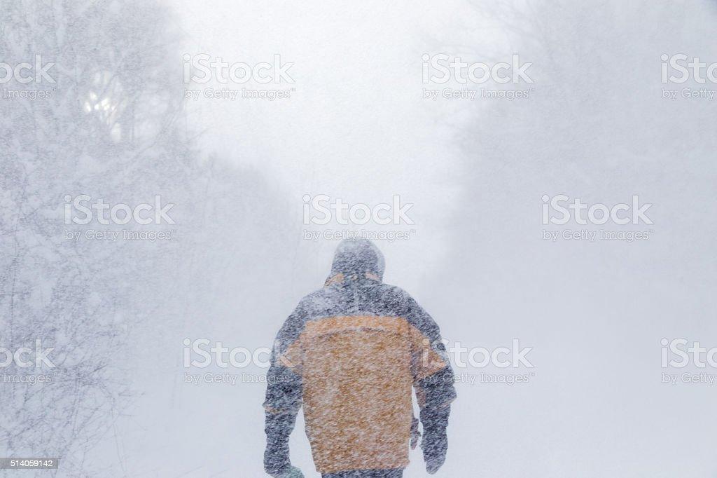Man walking in heavy snow storm stock photo