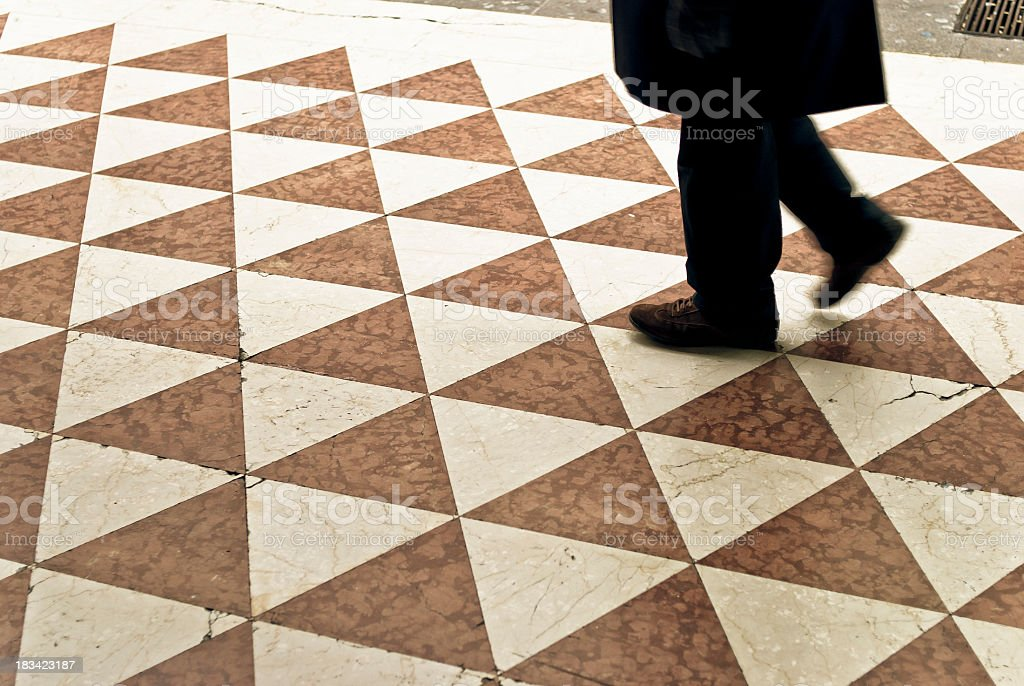 Man Walking In Milan City On A Triangular Tiled Floor stock photo