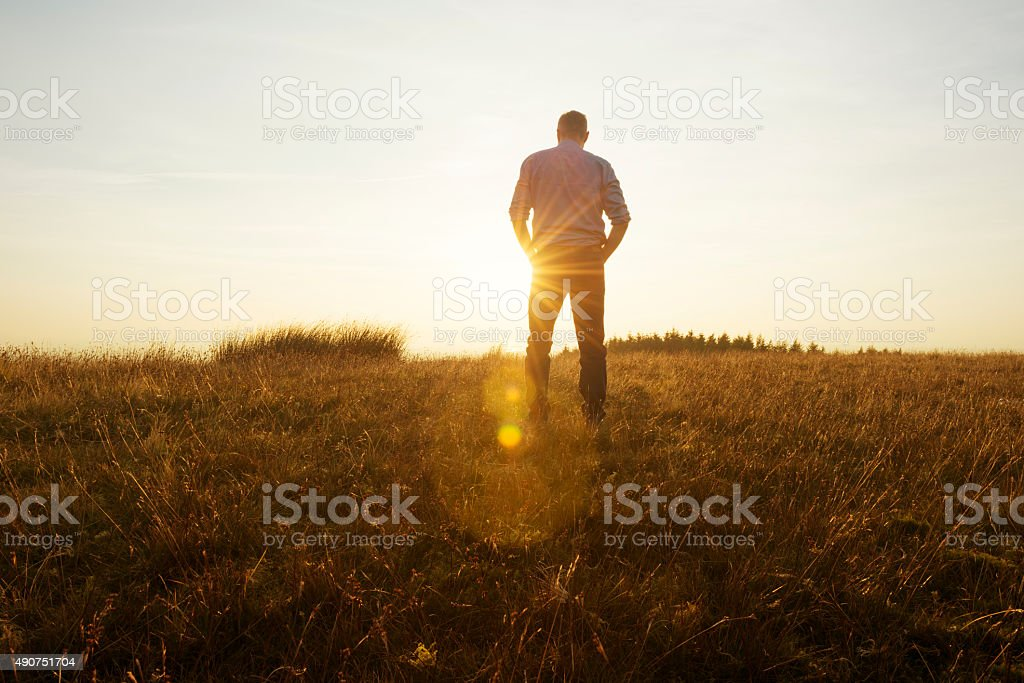 Man walking in the countryside looking at the sunset stock photo