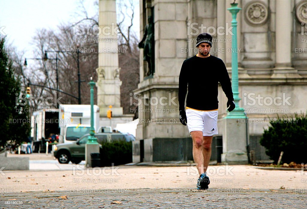 Man walking in white workout shorts on chilly day. stock photo
