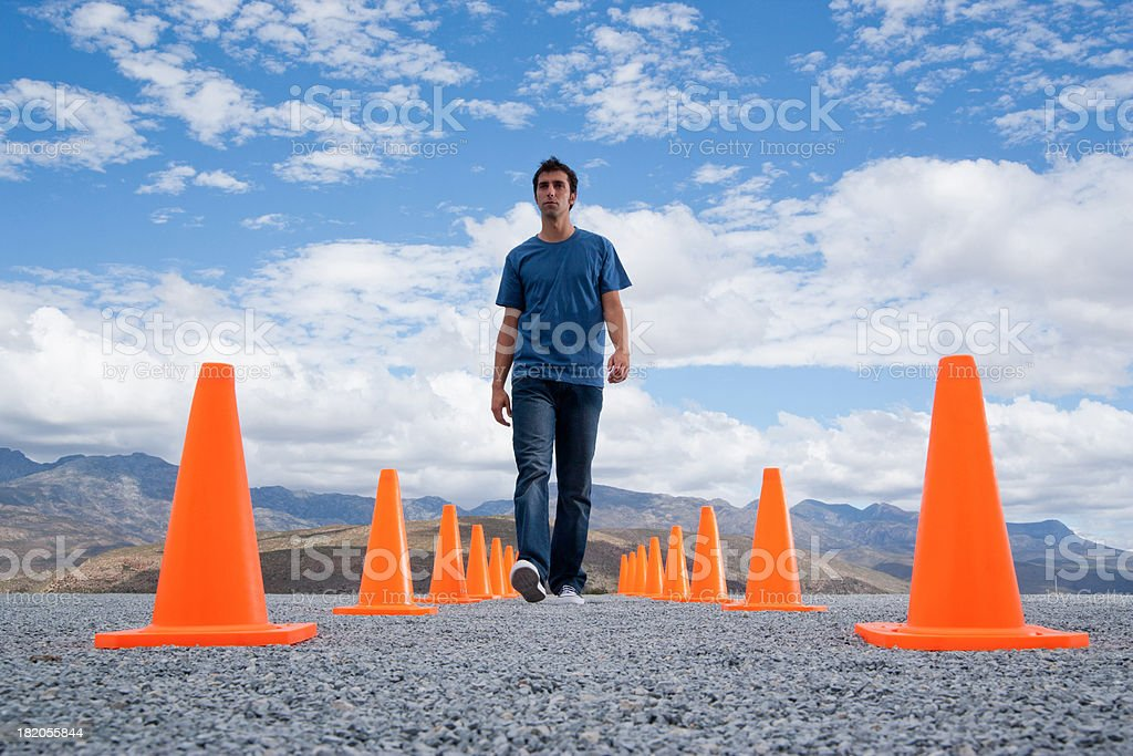 Man walking in-between two rows of safety cones stock photo