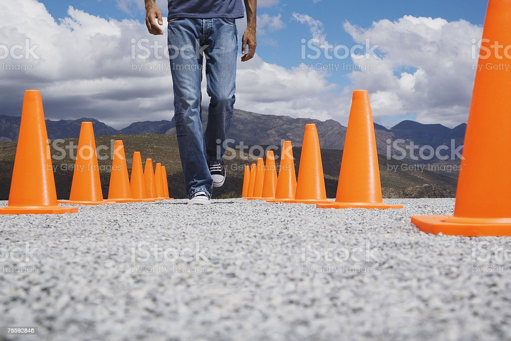 Man walking in-between two rows of safety cones royalty-free stock photo