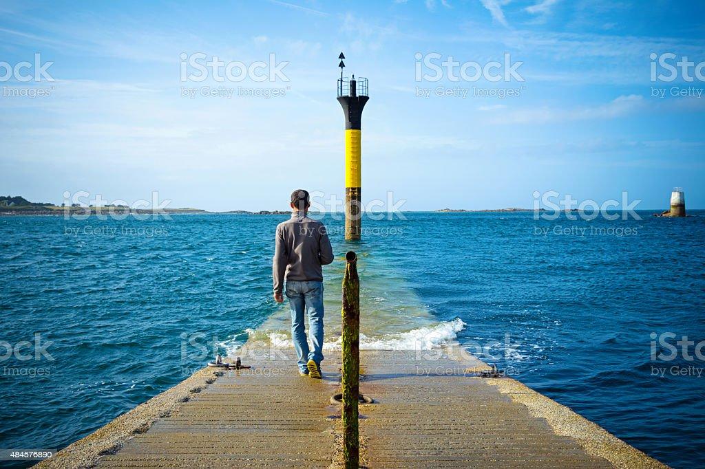 Man walking into the sea stock photo