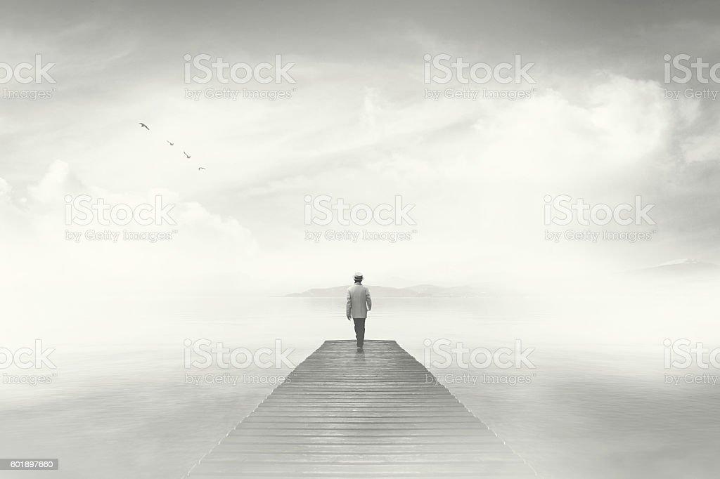Man walking on a boardwalk in the fog stock photo